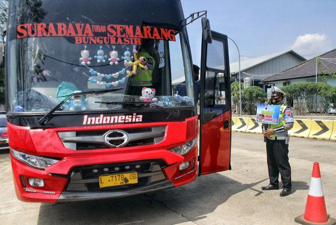 DIPERKETAT: Petugas memberhentikan kendaraan dari arah Jawa Timur di Jembatan Timbang Temperak, Sarang, Rembang kemarin.
