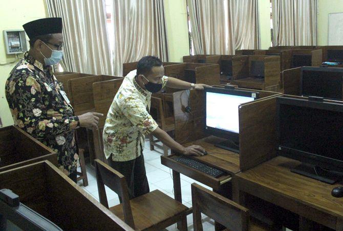 PERSIAPAN: Kepala SMPN 1 Jepara Ahmad Nurrofiq (kiri) didampingi teknisi komputer mengecek kesiapan perangkat untuk US SMP baru-baru ini.
