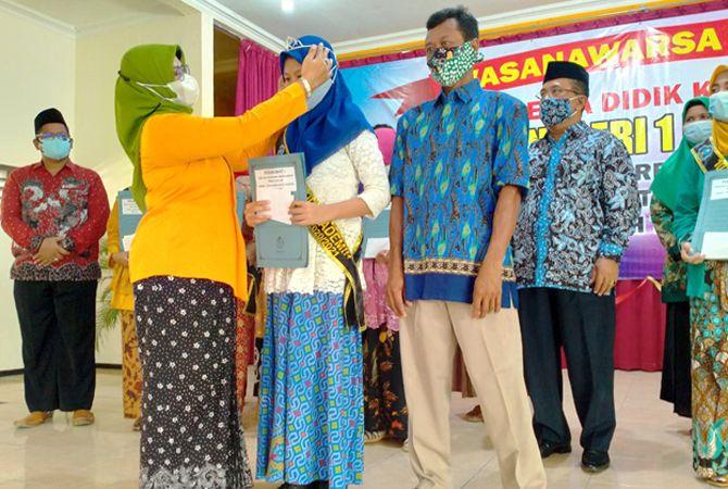 BERI REWARD: Kepala Sekolah SMPN 1 Rembang, Isti Choma Wati menyerahkan reward pada siswa berprestasi kompetensi akademik peringkat 10 besar berdasarkan nilai sekolah tahun pelajaran 2020/2021, Sabtu lalu (5/6).