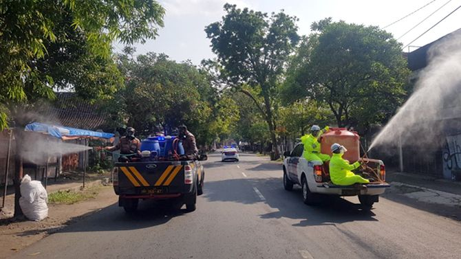 USIR VIRUS: Anggota Polres Grobogan menyemprotkan disinfektan di jalan protokol Kota Purwodadi.