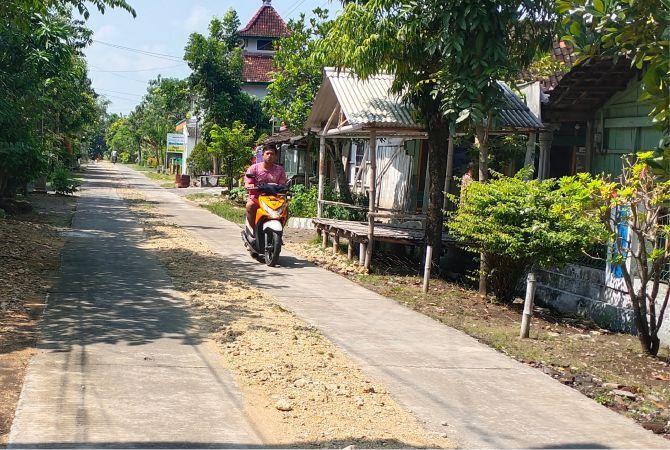MAYORITAS BAIK: Warga melintas di jalan desa milik Pemdes Kemloko, kemarin.