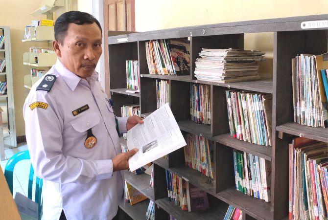 MILIKI PERPUS: Suyatin berada di perpustakaan yang letaknya jadi satu dengan Kantor Kepala Desa Kemloko, kemarin.