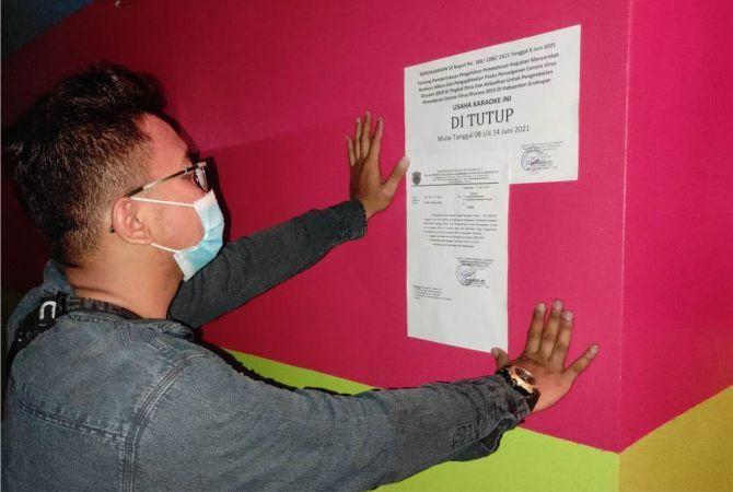 DISEGEL: Petugas dari Disporabudpar Grobogan memasang tanda  di tutup pada salah satu karaoke Kecamatan Gubug.