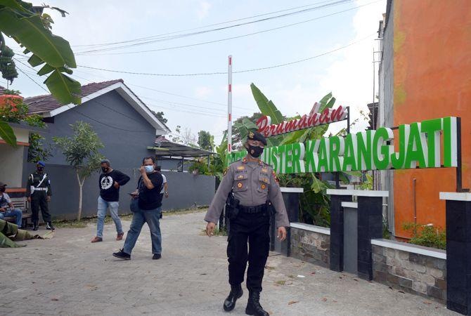 HARI KEDUA: Anggota polisi berjaga di pintu masuk Perumahan Grand Cluster Karangjati. Semua rumah KPR di perumahan tersebut disita Bareskrim Polri.