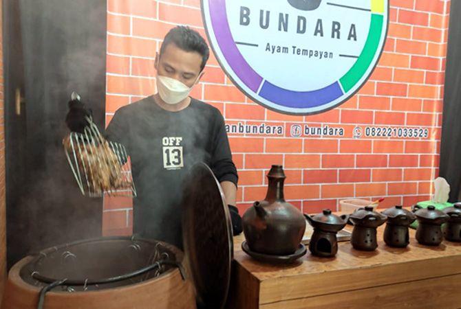 MASAK AYAM: Muhammad Arwani Amaludin memasak ayam tempayan menggunakan guci dari tanah liat di warungnya baru-baru ini.