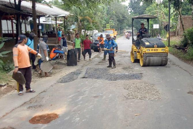 DIPERBAIKI: Petugas klinik jalan DPUPR Jepara menambal beberapa titik lubang di ruas jalan  raya Lebak, Pakisaji, kemarin. Ruas tersebut sempat ditanami pisang oleh warga.