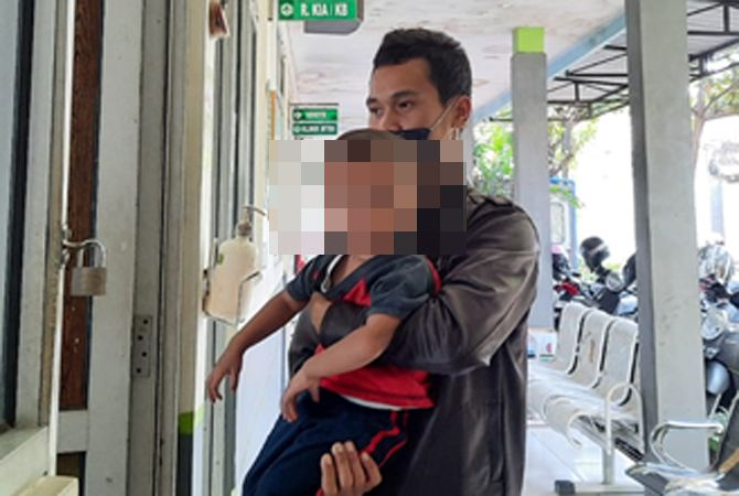 AYO IMUNISASI: Heri menggendong anaknya di depan ruangan imunisasi di Puskesmas Jati kemarin.