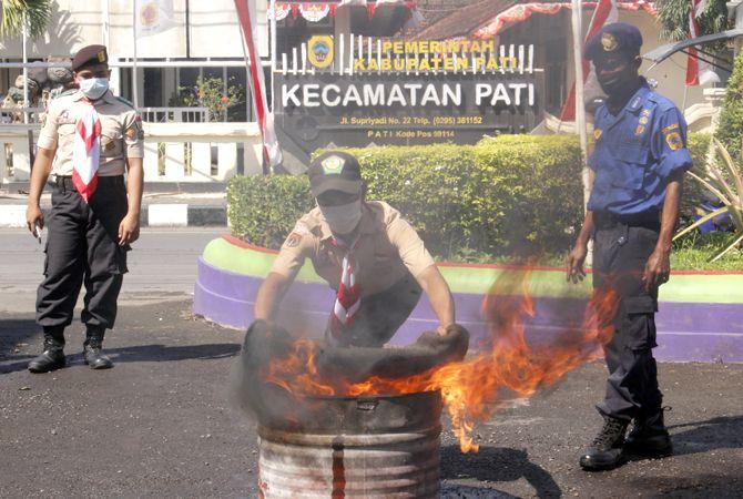 DILATIH: Salah satu peserta pelatihan Damkar mencoba memadamkan api di Pos Damkar Pati kemarin.