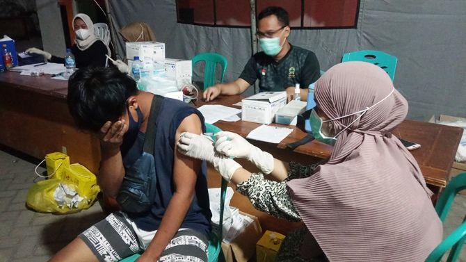 AWWW: Warga menutup mata saat disuntik vaksin. Vaksinasi di Karimunjawa berlangsung hingga malam hari.