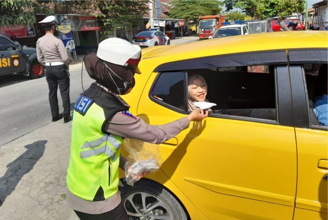 PROKES: Sat Lantas Polres Grobogan membagikan masker ke pengendara yang melintas.
