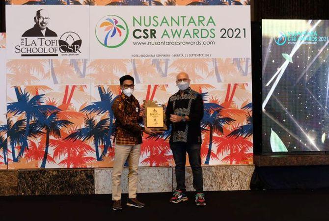 BERGENGSI: Perwakilan manajemen Semen Gresik (kiri) menerima penghargaan dari ketua Dewan Juri NCSR Award 2021 La Tofi.