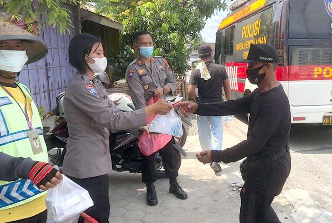 SERAHKAN SEMBAKO: Anggota Polres Grobogan memberi sarapn gratis kepada tukang becak di Purwodadi yang terdampak Covid-19.
