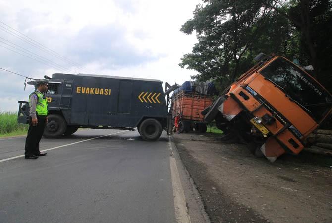 EVAKUASI: Truk gandeng nopol N 8380 US pengangkut kayu sengon terguling di bahu jalan ruas Sidorejo, Saradan.