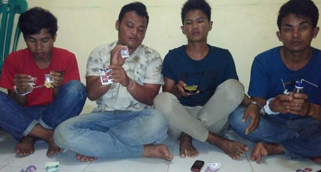 TERTANGKAP: Empat remaja menunjukkan barang bukti penggunaan narkoba setelah diringkus polisi di Pulau Kangean, Sumenep, Jumat malam (11/8).
