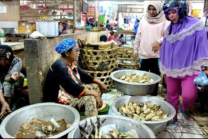 KAIS REZEKI: Pedagang ikan menunggu pembeli di Pasar Srimangunan, Sampang, Senin (6/11).