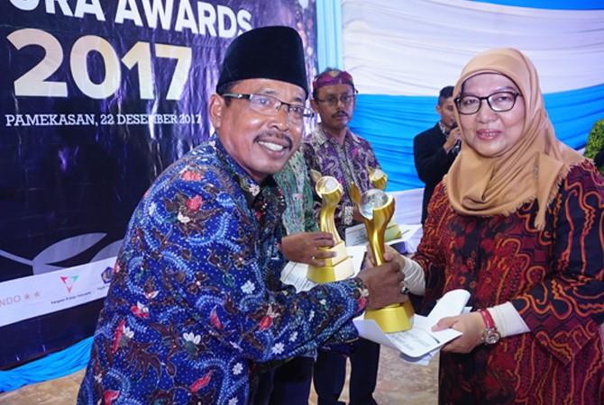 PATUT DICONTOH: Staf Ahli Bidang Pengembangan Ekonomi Lokal Kementerian Desa PDTT RI Ratna Dewi Andriani (kanan) memberikan penghargaan Madura Award kepada Ketua BUMDes Barokah Desa Labuhan Misnawar di Gedung Islamic Center Pamekasan, Jumat (22/12).