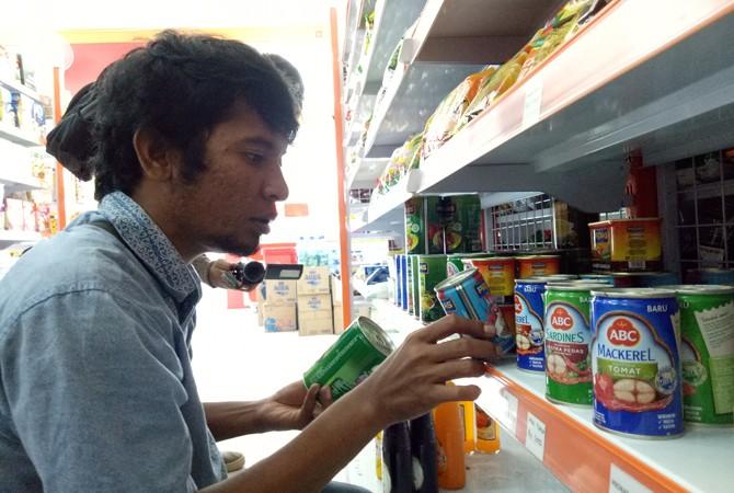MASIH BEREDAR: Warga menunjukkan produk makanan makarel yang masih tersedia di toko modern wilayah Kota Sampang, Selasa (3/4).