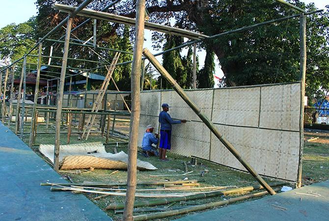BELUM RAMPUNG: Para pekerja masih menggarap pembuatan stan PRB di Alun-Alun Bangkalan, Rabu (10/10).