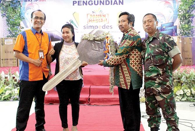 SIMBOLIS: Asisten I Setkab Sampang Nurul Hadi (pakai batik) didampingi AMBM BRI Cabang Sampang Arif Wahyudi (kiri) beserta perwakilan Dandim 0828 Sampang memberikan kunci kendaraan Ertiga kepada pemenang undian, Kamis (18/10).