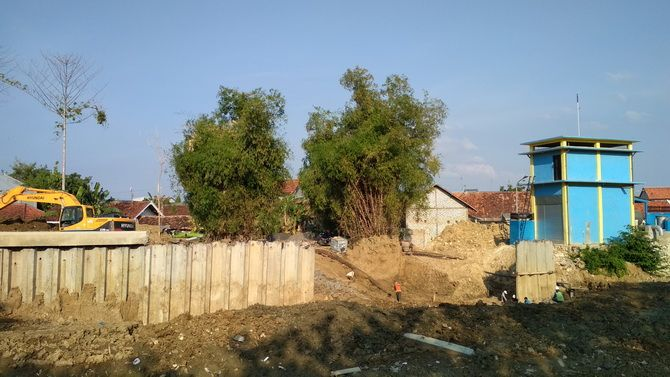KEBUT: Pekerja sedang memperbaiki sheet pile Kali Kamoning yang nyaris roboh.