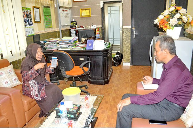INOVATIF: Kepala BKPSDM Sumenep R Titik Suryati (kiri) menunjukkan cara kerja Smart ID Card kepada juri Madura Awards Mohamad Harun.