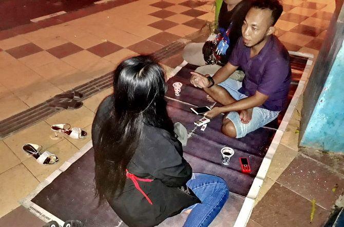 BUTUH SOLUSI: Eks pemandu lagu berbincang dengan warga di trotoar sekitar Arek Lancor Pamekasan, Sabtu (5/1).