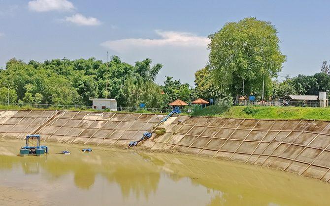 SEGERA DIKEMBANGKAN: Warga melintas di sekitar Embung Samiran, Desa Kodik, Kecamatan Proppo, kemarin.