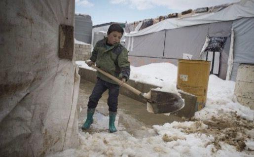 MELAWAN DINGIN: Bocah pengungsi Suriah saat membersihkan tumpukan salju menggunakan sekop.