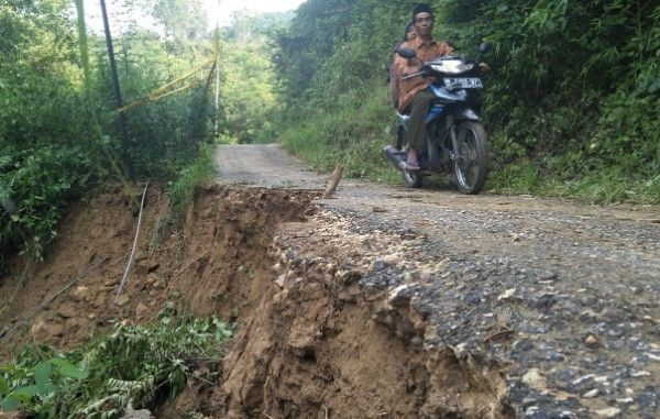 AMBLES: Pengendara sepeda motor saat melewati jalan penghubung Desa Basoka dan Desa Gadu Barat yang longsor, Minggu (10/2).