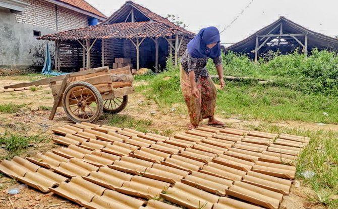 KERJA KERAS: Seorang warga Desa Palengaan Laok, Kecamatan Palengaan, memindahkan genting kemarin.