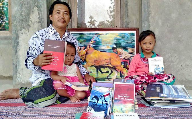 BERSAHAJA: Harkoni bersama anaknya, Githa dan Aliya menunjukkan buku Antologi Puisi Nusantara di rumahnya di Desa Jatra Timur, Kecamatan Banyuates, Sampang, Sabtu (9/2).