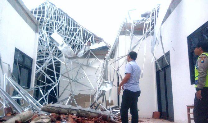 AMBRUK: Polisi berada di lokasi Puskesmas Torjun yang ambruk tak lama setelah putus kontrak karena melewati tahun anggaran.