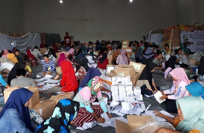 SEMANGAT: Ratusan petugas sedang menyortir dan melipat surat suara di gudang yang terletak di Jalan KH Mansyur, Kota Sumenep, kemarin.