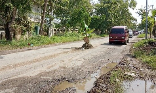 PELAN-PELAN: Mobil carry melintas di Jalan Raya Bancaran yang rusak, Jumat (15/3).