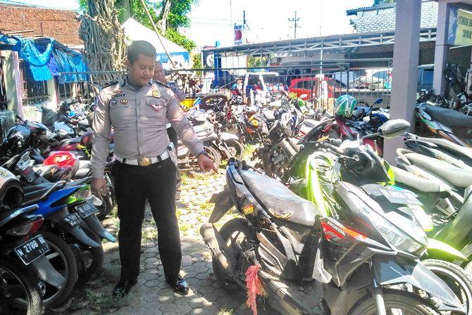 MAKAN KORBAN: Kanit Laka Lantas Polres Bangkalan Ipda Didit Permadi menunjukkan kendaraan yang terlibat laka di halaman kantor Unit Laka Lantas kemarin.
