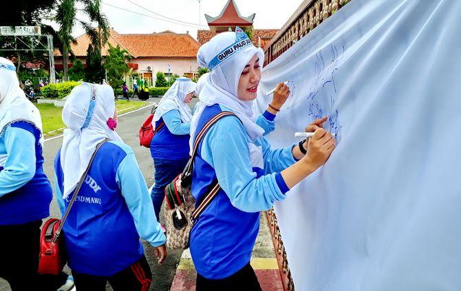SAMPAIKAN ASPIRASI: Guru PAUD di Pamekasan menandatangani petisi di atas kain putih kemarin.