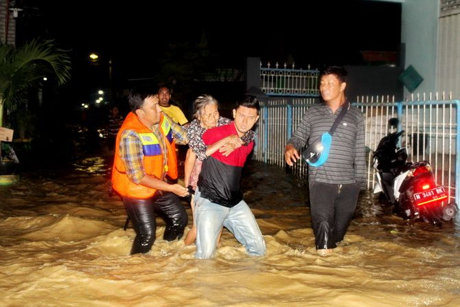 BANTU NENEK: Warga lanjut usia terdampak luapan sungai di Jalan KH Hasan Shinhaji,Kelurahan Jungcangcang, Pamekasan, dievakuasi Sabtu malam (13/4).