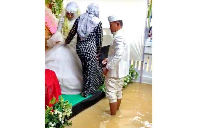 TAK KAN LUPA: Pasangan pengantin Bambang Yuda Harmoko dan Reni Faradila Sari berada di kursi pelaminan yang tergenang banjir di Sampang kemarin.