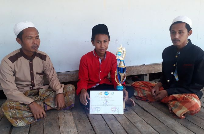 MEMBANGGAKAN: Moh. Amirul Islam (tengah) menunjukkan piala dan sertifikat didampingi Manajer Bahasa Mandarin Yusril Huda (kanan) dan Iswandi di LPI Al-Majidiyah Pamekasan kemarin.