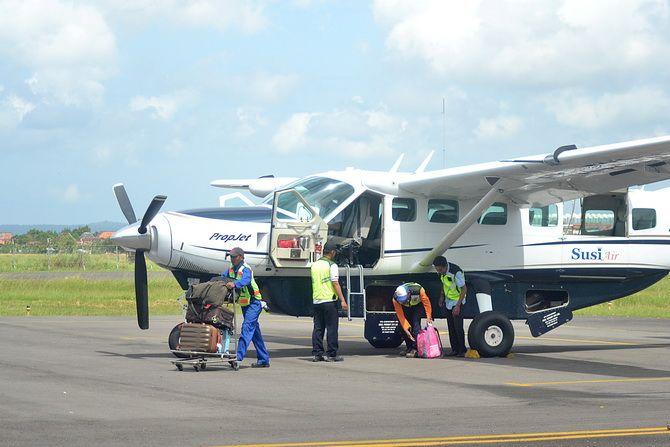 BEROPERASI: Petugas membantu membawa barang bawaan penumpang dari bagasi pesawat Susi Air di Landasan Bandara Trunojoyo Sumenep kemarin.