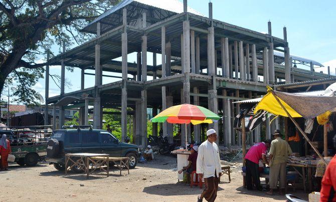 BELUM TUNTAS: Masyarakat beraktivitas di sekitar proyek pembangunan Pasar Lenteng, Sumenep, kemarin.