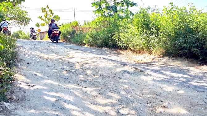HATI-HATI: Pengendara motor melintasi jalan yang rusak di Desa Patarongan, Kecamatan Torjun, kemarin.