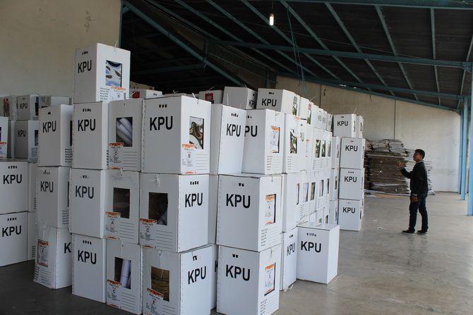 LENGANG: Warga berada di sekitar tumpukan kotak suara di gudang penyimpanan logistik pemilu di Kelurahan Bugih, Kecamatan Kota Pamekasan, kemarin.