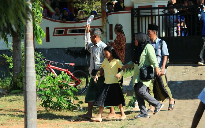 KEHILANGAN: Sifa dipapah kakek dan neneknya saat datang ke kecamatan untuk melihat jenazah orang tuanya