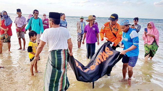 TAK BERNYAWA: Tim Basarnas Jatim dibantu warga mengevakuasi jasad Muhammad Rizal di pinggir pantai Desa Lapa Laok, Kecamatan Dungkek, Sumenep, kemarin.