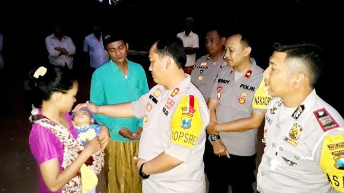 PEDULI: Kapolres Bangkalan AKBP Boby Pa'ludin Tambunan mengusap kening Kholilur Rohman, pengidap jantung bocor di kediamannya kemarin petang.