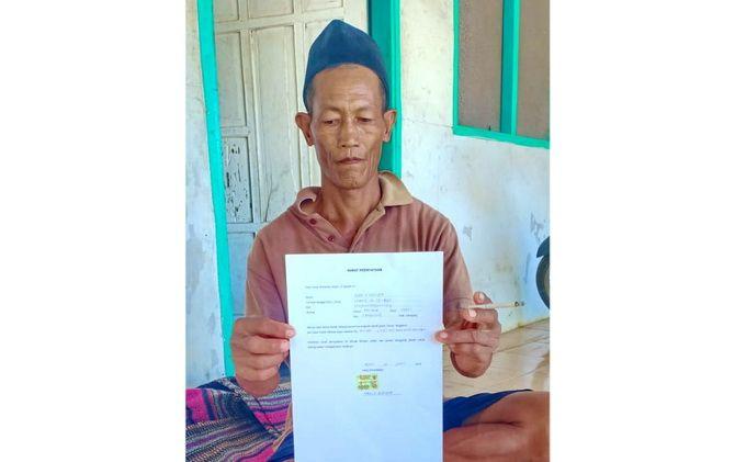 BEBER: Hadi P Misriyah, 54, warga Desa Sejati, Kecamatan Camplong, Sampang, menunjukkan surat pernyataan bahwa dipungut biaya saat memasang listrik gratis kemarin.