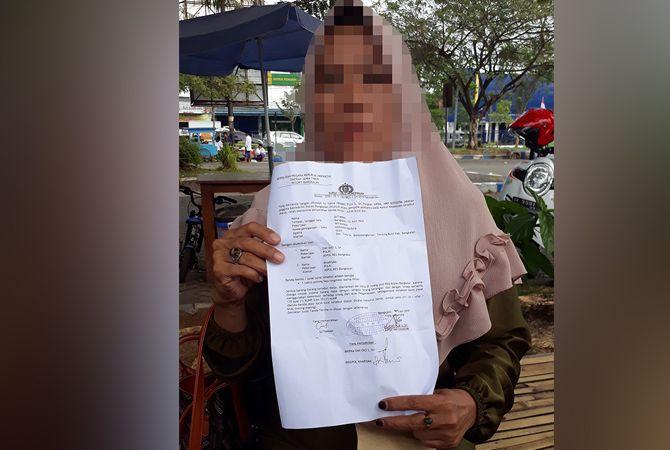 MINTA KEADILAN: Perempuan berinisial S menunjukkan bukti surat penerimaan laporan dari Polres Bangkalan kemarin siang.
