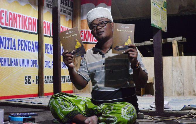 BERDEDIKASI: Alfaizin Sanasren menunjukkan buku karangannya yang berjudul Talken Koneng saat ditemui di kediamannya di Desa/Kecamatan Batuan, Sumenep, Senin malam (8/7).