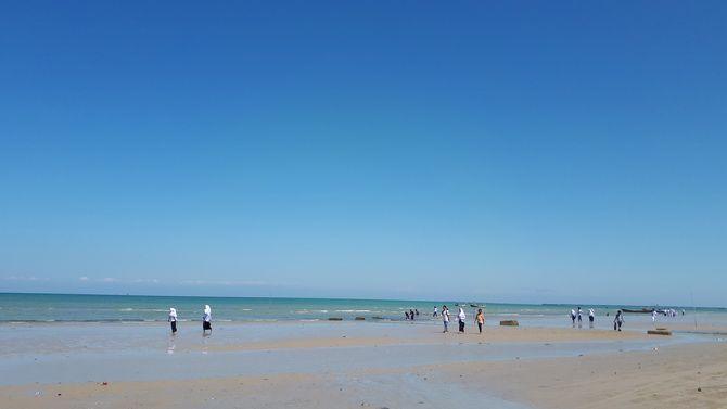 SEDANG SURUT: Puluhan wisatawan lokal sedang bermain di Pantai Camplong saat air surut kemarin.